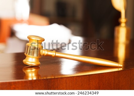 Juridical concept with hammer and lawbook, selective focus on metal part - stock photo