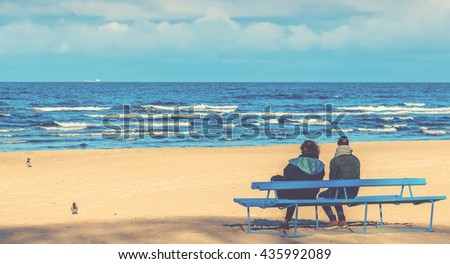 JURMALA, LATVIA - NOVEMBER 08, 2014: Coastal landscape with sandy beach of the Baltic Sea and men looking at marine ships on horizon
