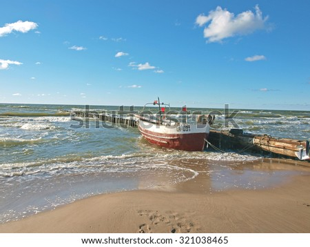 JURMALCIEMS, LATVIA - SEPTEMBER 27, 2015: Fishing boat is towed at small old wooden pier.        - stock photo