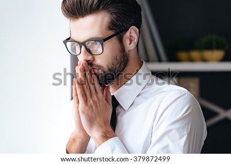 Just a moment to overthink everything. Handsome young businessman in glasses looking thoughtful and keeping hands clasped while standing in office - stock photo