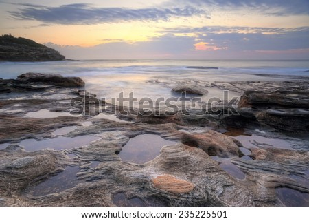 Just after sunrise on the rockshelf at Mackenzies Bay Sydney Australia - stock photo