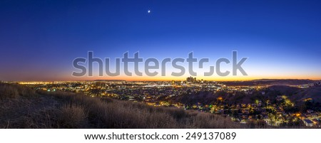 Just after sunset, the glow of the sun remians behind downtown LA, and the moon has already risen. - stock photo