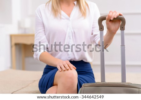 Just arrived. Attractive young woman sitting at the edge of bed in her hotel room.  - stock photo