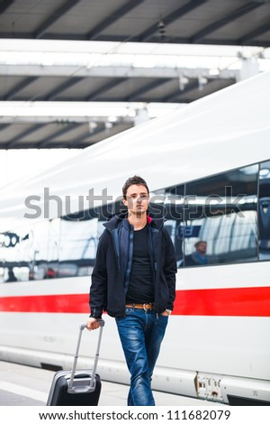 Just arrived: handsome young man walking along a platform at a modern train station - stock photo