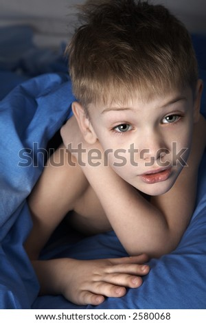 just awakened boy in blue bedclothes