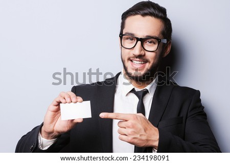 Just call this number! Handsome young man in formalwear stretching out a business card while standing against grey background