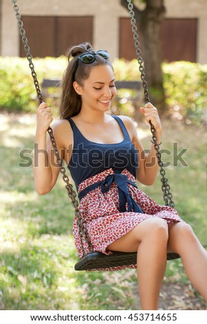 Just enjoy yourself, brunette beauty having fun with swing in summer sunshine. - stock photo