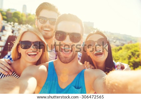 Just for fun. Group of cheerful young people bonding to each other and making selfieon camera while having fun on the roof - stock photo
