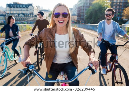 Just friends and road ahead. Beautiful young smiling woman riding bicycle and looking at camera while her friends riding in the background - stock photo