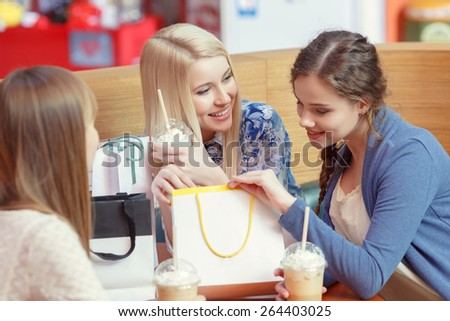 Just have a look at this wonder. Happy young girls look inside the shopping bag with excitement and discussing their purchases by the cocktail - stock photo