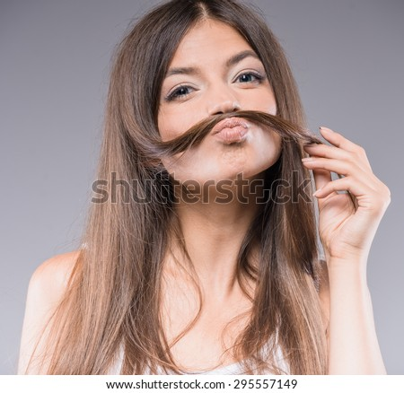 Just having fun. Beautiful young woman holding fake mustache on her face and smiling over gray background. - stock photo