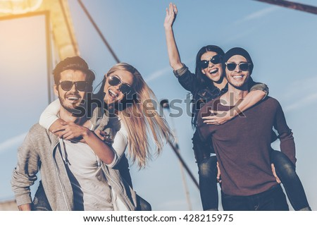 Just having fun. Two handsome young men piggybacking their girlfriends and smiling while walking along the bridge - stock photo