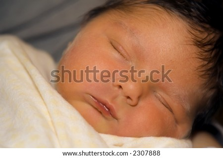Just home from the hospital this newborn baby girl rests while wrapped in a blanket. - stock photo