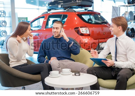 Just imagine  we bought a car. Young male customer talking over the phone and female customer showing delight about the purchase of the car with the sales consultant by the table and a blurred red - stock photo