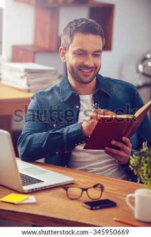 Just inspired. Handsome young man looking at his notebook and smiling while sitting at his working place in office - stock photo