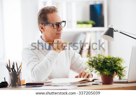 Just inspired. Thoughtful mature man holding hand on chin and looking away with smile while sitting at his working place - stock photo