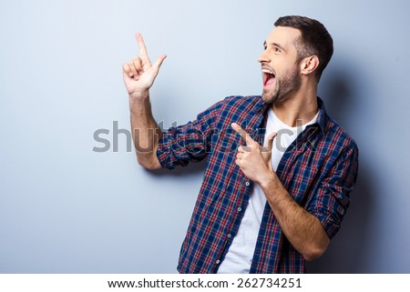 Just look at that! Happy young man in casual shirt pointing away and smiling while standing against grey background - stock photo