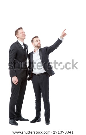 Just look at this! Full length of two happy young businessmen pointing copy space and smiling while standing isolated on white
