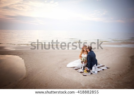Just married bride and groom sit on the beach in their honeymoon