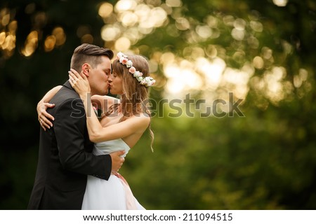 Just married couple embrace, wedding pair hugging, Bride and Groom, Romantic Married Couple at sunset, holding hands, beautiful couple in the sun, They Hug each other, wedding, kissing couple - stock photo