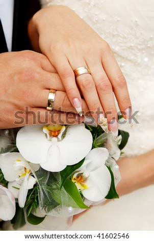 Just married couple hands on a bouquet