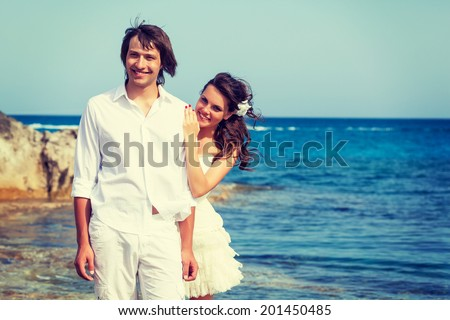 Just married couple is standing near the sea - stock photo