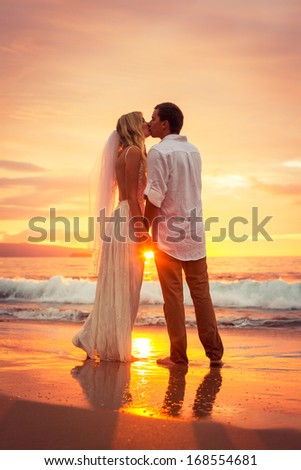 Just married couple kissing on tropical beach at sunset, Hawaii Beach Wedding, Intimate loving moment - stock photo
