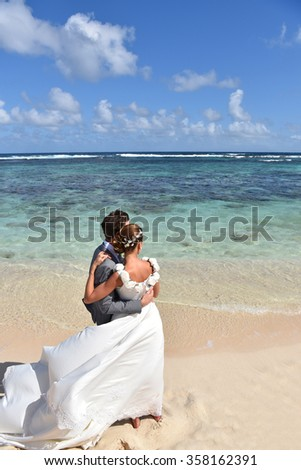 Just married couple on the beach looking towards the skyline