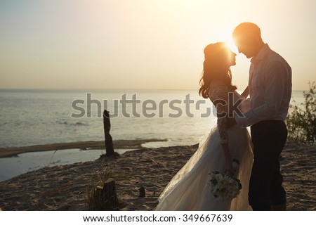 Just married couple running on a sandy beach - stock photo