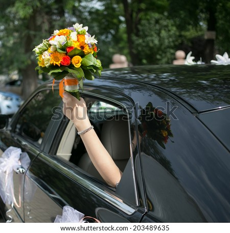Just married couple together in a car. Happy bride holding up wedding flowers. focus on flowers - stock photo