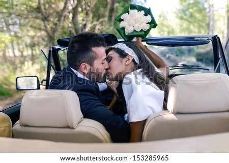 Just married couple together in an old car - stock photo