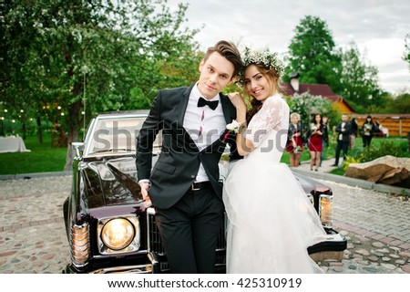 Just Married embracing at a wedding. Bride put a hand on Groom shoulder. Standing near retro car. They pose for a photograph on the camera. Outdoor - stock photo