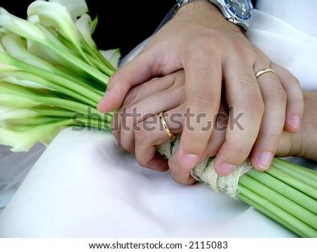 Just married groom and bride holding hands with rings. - stock photo