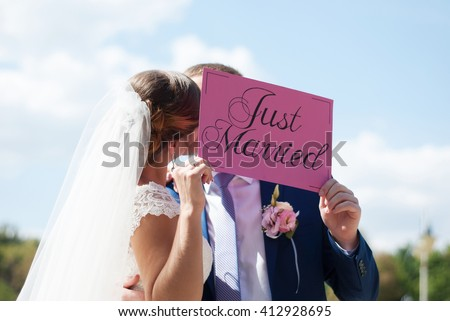 "Just married happy couple. Wedding celebration. Newlyweds are kissing with a sign ""Just married"" in their hands. Wedding couple kiss. - stock photo"