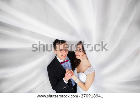 Just married laughing under a veil - stock photo