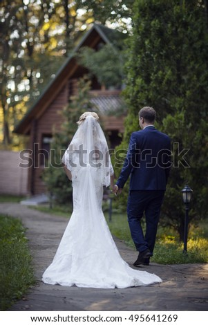 Just married loving hipster couple in wedding dress and suit on village road in a forest at sunset. happy bride and groom walking running and dancing in the summer meadow. Romantic  young family