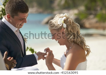 Just married newlyweds couple exchange rings, groom puts the ring on the bride's hand during beautiful tropical ceremony. - stock photo