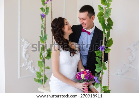 Just married play, bride sitting on a swing with the vine - stock photo