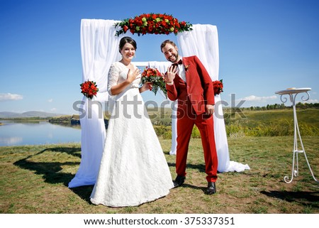 Just married positive bride and groom show rings after the wedding ceremony on background of arch with red flowers and white cloth, outdoors, on banks of the river. Marsala color and decoration style. - stock photo