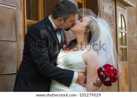 Just married young couple kissing in front of the house