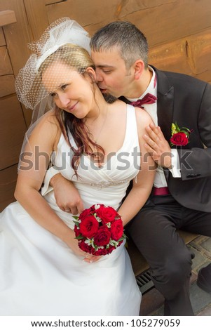 Just married young couple sitting on the porch and kissing - stock photo