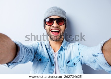 Just me and no one else. Top view of handsome young man in hat and sunglasses making selfie and smiling while standing against grey background - stock photo