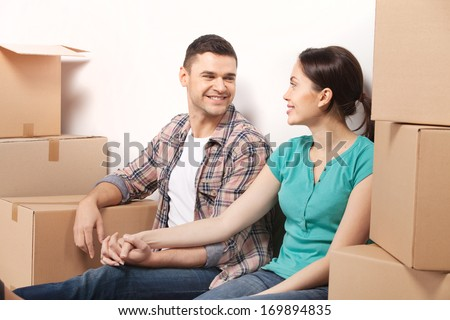 Just moved in a new apartment. Beautiful young loving couple sitting on the floor and holding hands while cardboard boxes laying around them