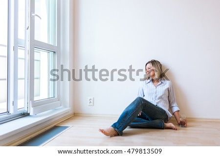 Just moved in: beautiful young woman having a drink in her brand new modern apartment