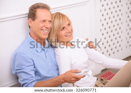 Just relax. Nice smiling adult couple holding remote control and bonding to each other while watching television - stock photo