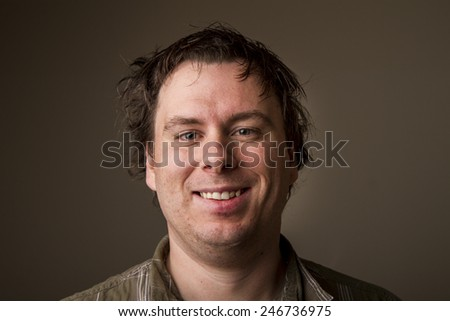 Just some dude making some weird smile with messy hair - stock photo
