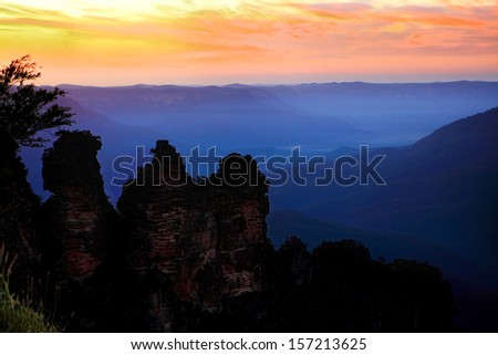 Just the three of us.  The dramatic  sunrise on a spring morning against the silhouetted iconic landmark, The Three Sisters, at Echo Point, Blue Mountains, Australia.  Image has some grain. - stock photo