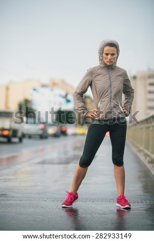 Just try to stop me once I start running. A woman is standing with a fiercely determined attitude, focused on running despite the rain. - stock photo