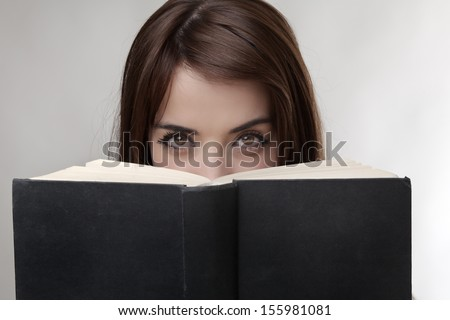 just woman eyes peering over a hard back book - stock photo