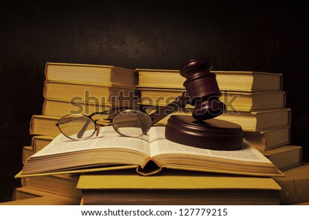 Justice gavel and eye glasses on pile of law books - stock photo